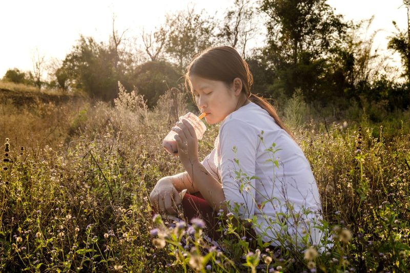 Rest, drink and sit and watch nature Relaxing Juice Daylight Nature Drink Plant One Person Leisure Activity Field Nature Women Growth Grass Land Sunlight Young Women Tranquility Outdoors Flower Lifestyles Beauty In Nature Flowering Plant