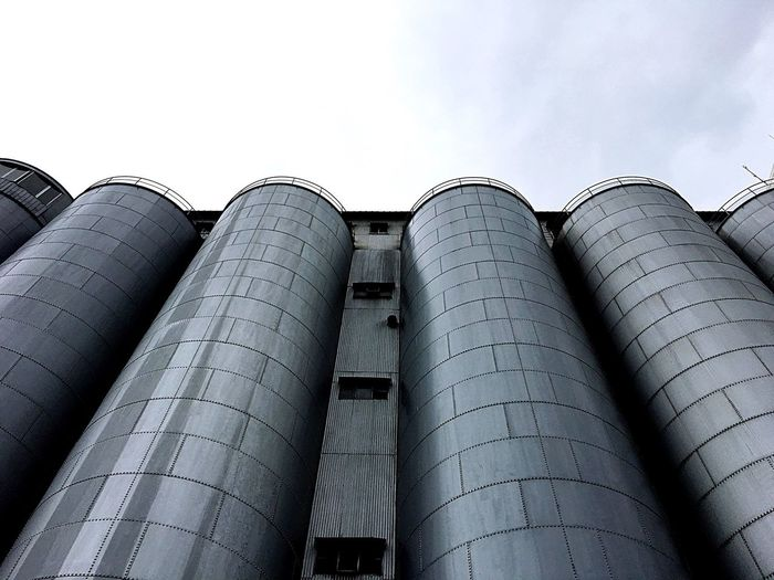 Low angle view of industry against cloudy sky