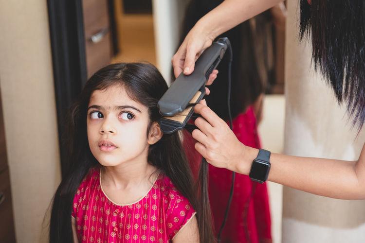 Hairdresser straightening the hair of girl