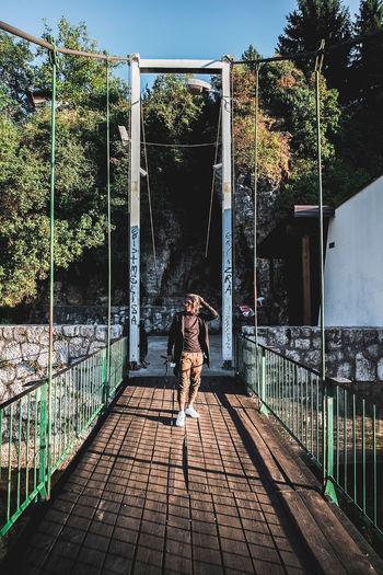 Woman walking on footpath by footbridge