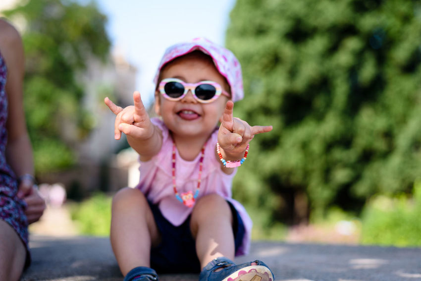 Infant girl with sunglasses and bandanna showing the 'Metal Hand' Children Fun The Week On EyeEm Casual Clothing Child Childhood Close-up Day First Eyeem Photo Girls Happiness Heavy Metal Human Hand Infant Leisure Activity Metal Hand Nature Outdoors Playing Sitting Sunglasses This Is Family