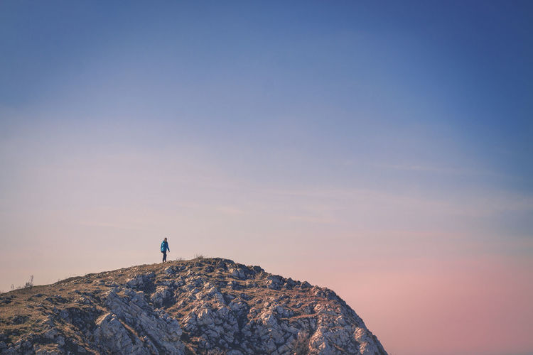Person Standing On Cliff Against Clear Sky During Sunset