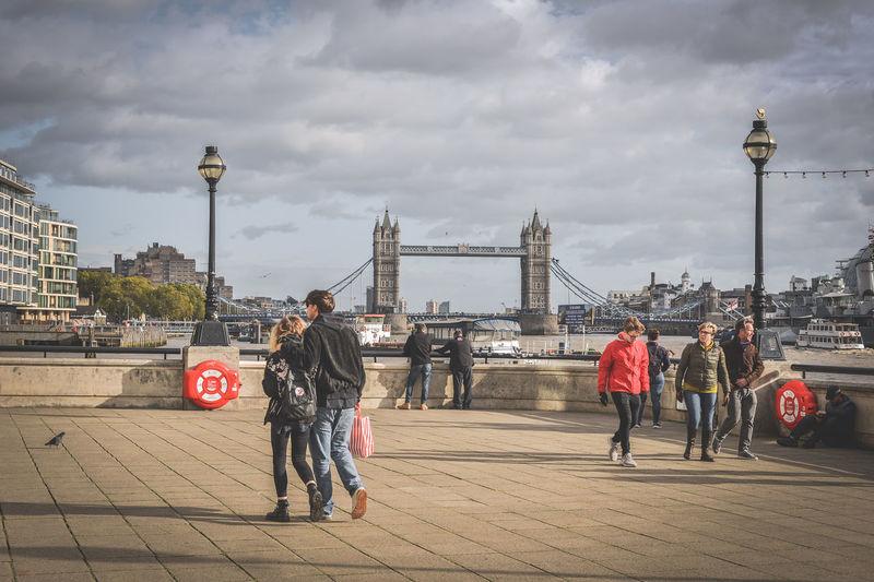People on bridge against cloudy sky