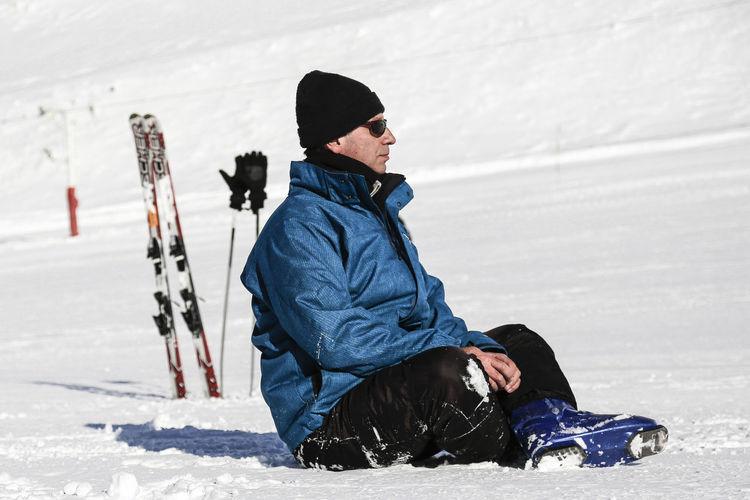 Male Skier Sitting On Snow