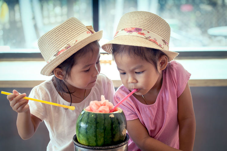Close-up of twin sisters having drink in restaurant