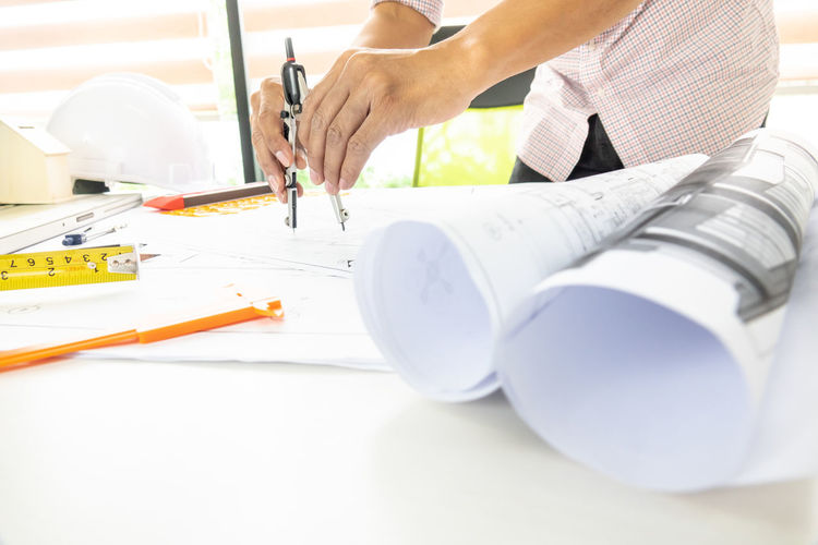 Midsection of male architect working on blueprint at desk in office