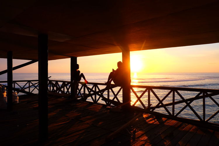 Silhouette People Sitting On Railing By Sea Against Sky During Sunset