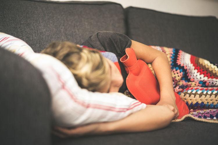 Boy sleeping on sofa at home