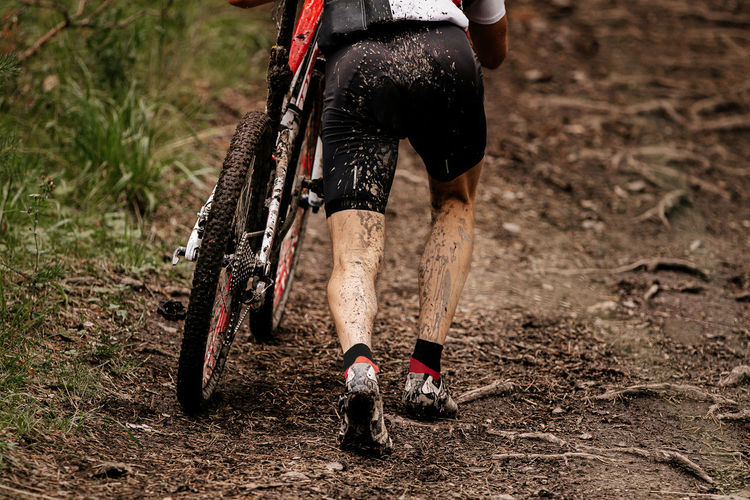 Low section of man with bicycle walking on dirt road
