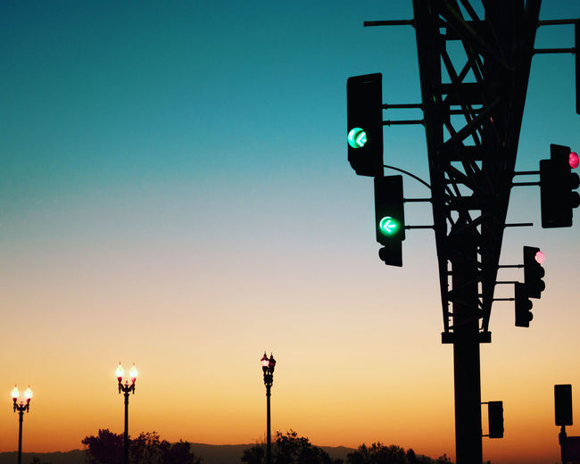 Low angle view of illuminated street lights against clear sky