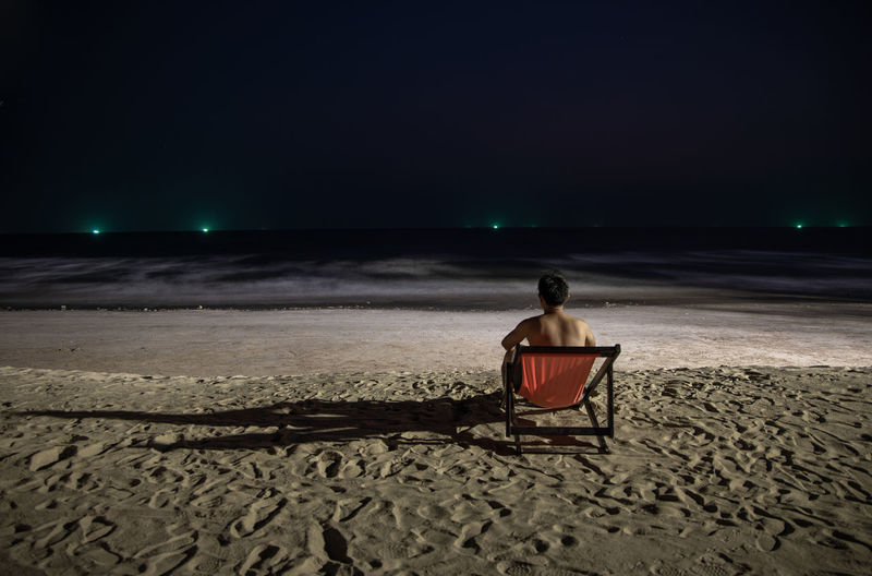 Rear view of man sitting on chair at beach during night