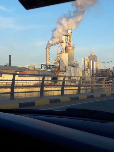 Smoke emitting from factory against sky