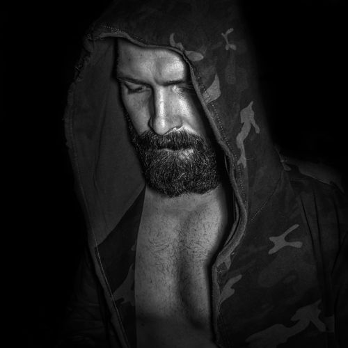 Close-up of bearded man wearing hooded shirt against black background