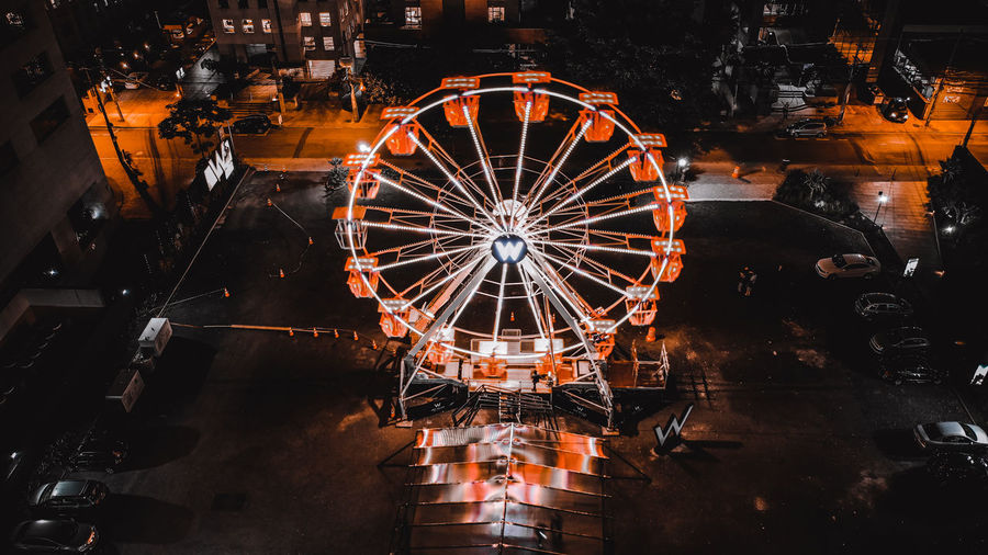 Aerial view of illuminated ferris wheel at night