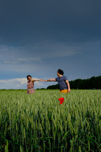 Couple holding hands while standing amidst plants on field against sky