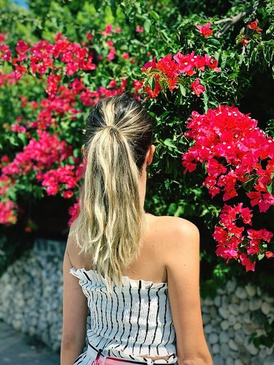 Rear view of woman standing against flowering plants