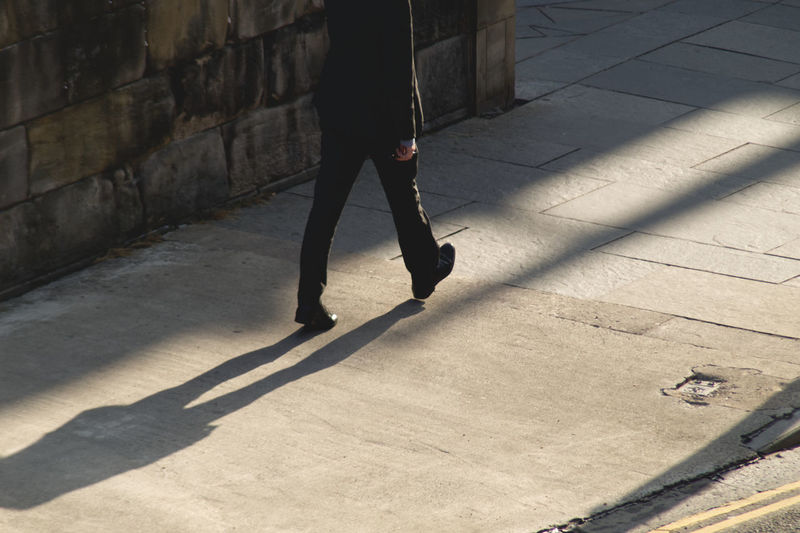 Low section of person walking on street