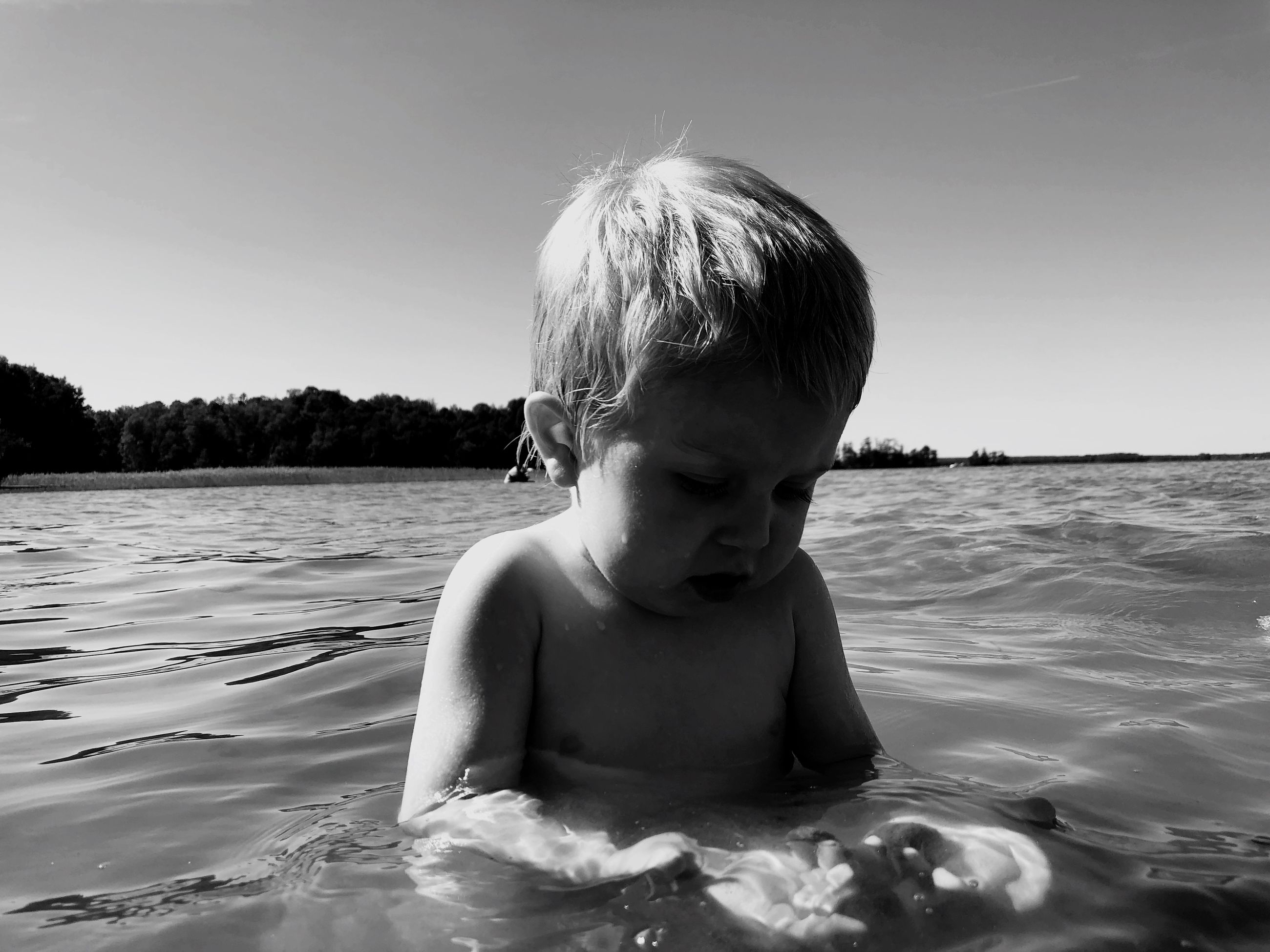 water, child, real people, childhood, one person, leisure activity, sky, sea, men, shirtless, lifestyles, headshot, waterfront, nature, looking, day, innocence, outdoors