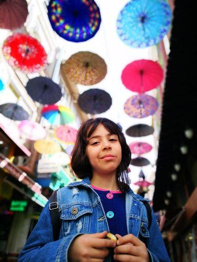 Portrait Of Girl Standing Against Multi Colored Umbrellas