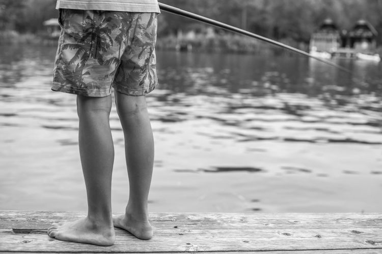 Low section of boy fishing in lake from pier