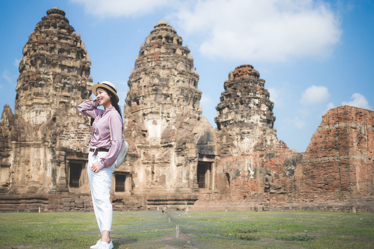 Smiling woman standing on land against old temples