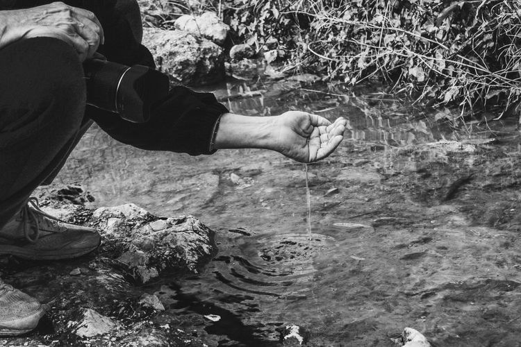Low section of photographer capturing water slipping from hand by river