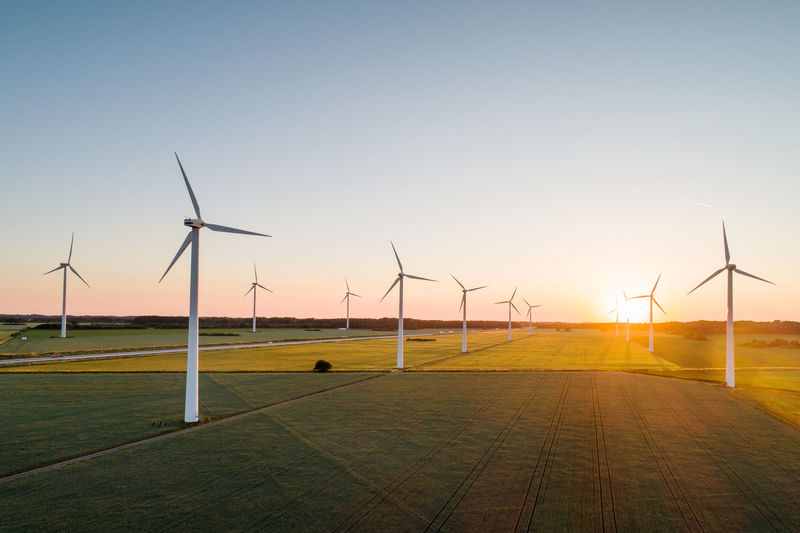 Wind turbines on field against clear sky during sunset