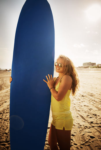 Smiling woman holding surfboard standing on beach