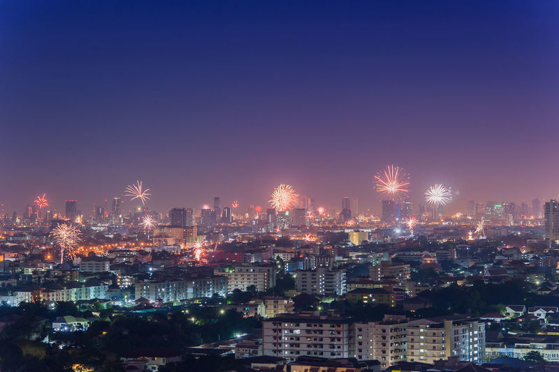 Firework exploding over illuminated cityscape at night