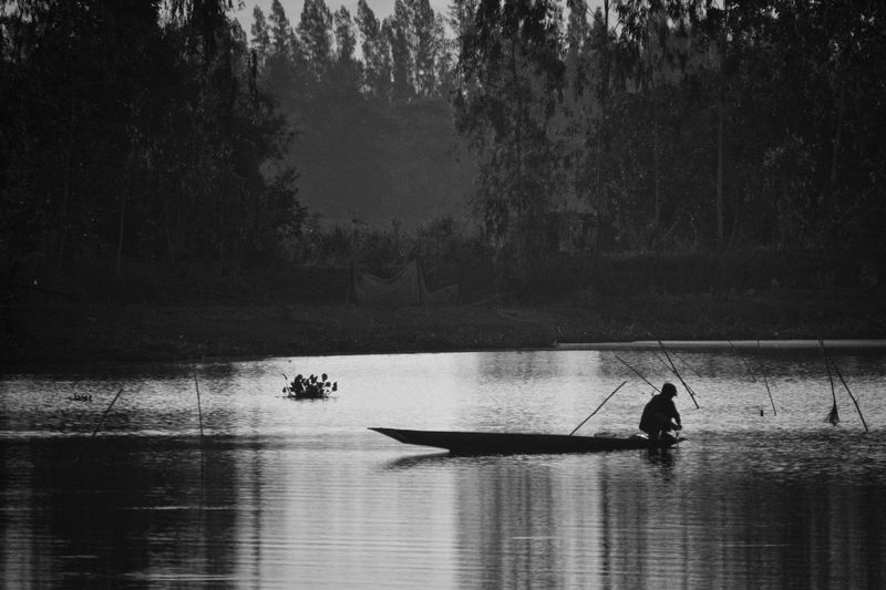 Fisherman Real People Water Tree Men Nature Transportation Waterfront Nautical Vessel Silhouette Outdoors One Person Lake Rowing Day Standing Occupation Beauty In Nature Scenics Oar Sky The Street Photographer - 2017 EyeEm Awards