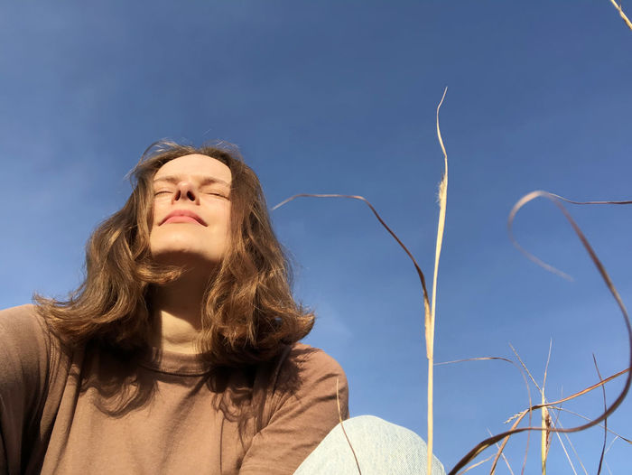 Low angle portrait of woman standing against blue sky