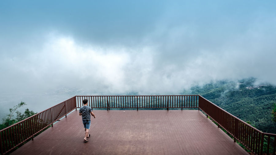 Rear view of man walking at observation point by mountains against cloudy sky