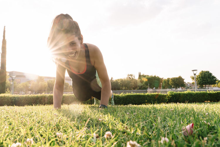 Portrait of teenage girl on field against sky