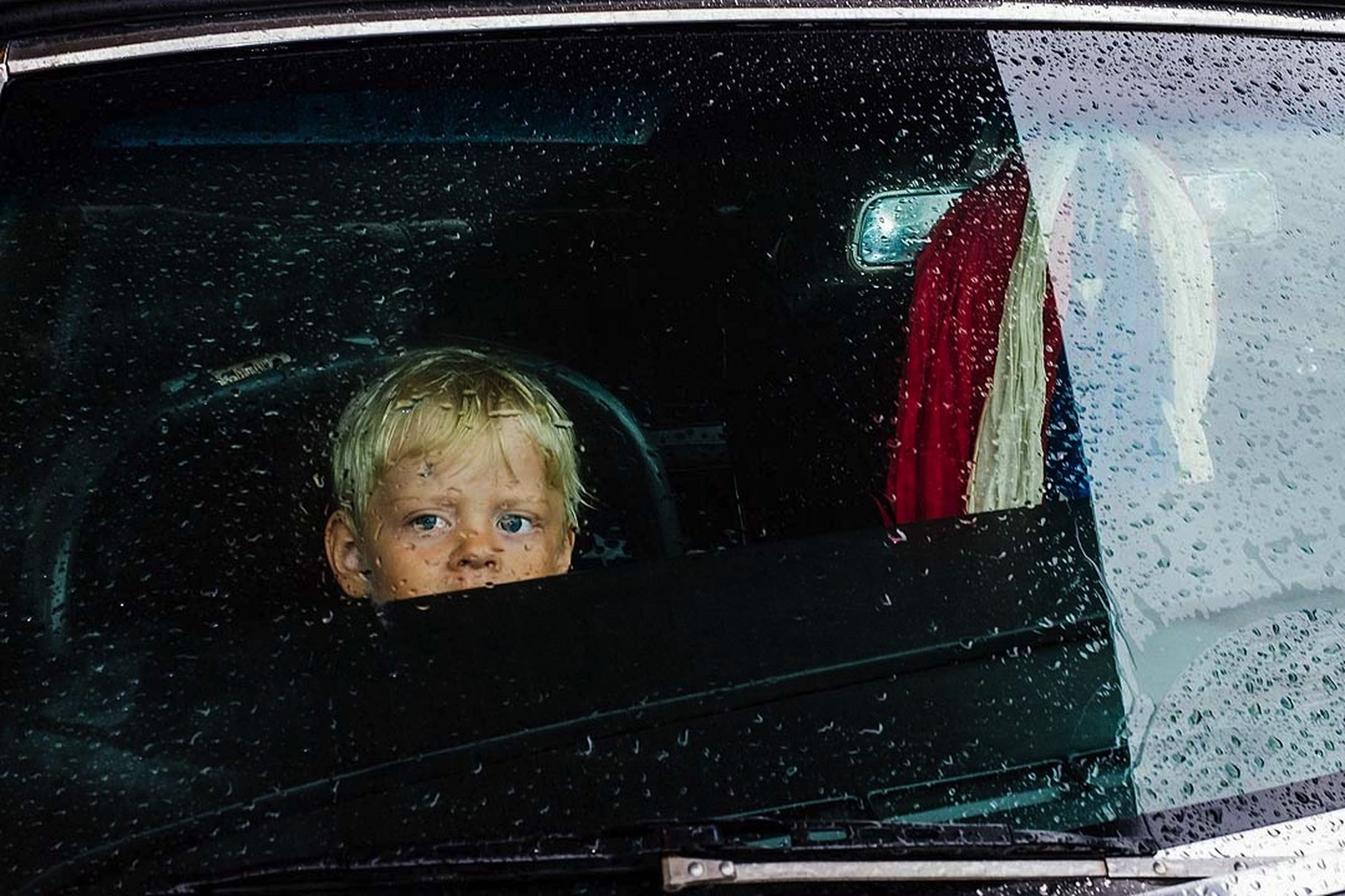 portrait, child, childhood, looking at camera, headshot, males, one person, mode of transportation, real people, men, glass - material, transportation, car, blond hair, front view, boys, motor vehicle, outdoors, rain, innocence