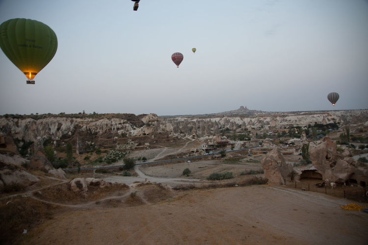 Hot air balloons flying over landscape