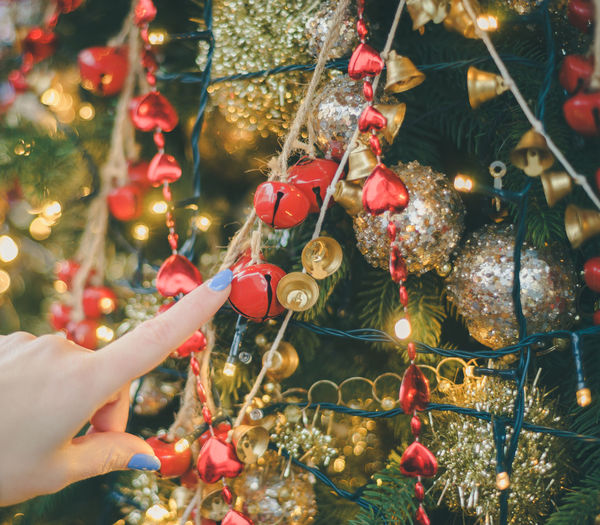 Cropped Hand Of Woman Touching Christmas Tree