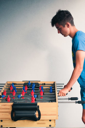 Side view of teenage boy playing foosball against wall at home