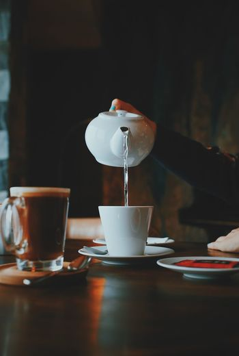Cropped Hand Of Woman Pouring Water In Coffee