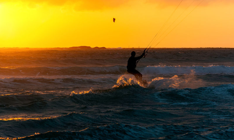 Sunset Sea Sport Sky Water Real People Leisure Activity Lifestyles Extreme Sports One Person Beauty In Nature Silhouette Waterfront Wave Motion Orange Color Aquatic Sport Adventure Surfing Horizon Over Water Kiteboarding Outdoors