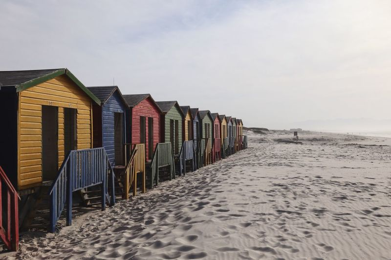 Hooded beach chairs on sand against sky
