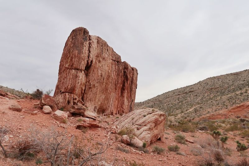 Rock formation on mountain against cloudy sky