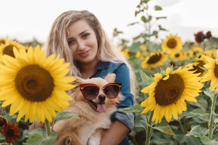 Portrait of young woman with sunflower