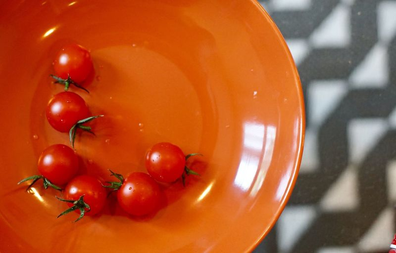 Baby tomato on orange plate Close-up Fruit Healthy Eating No People Wellbeing Food Tomato Focus On Foreground Nature Indoors  Still Life Orange Color Bowl Day Freshness Food And Drink Vegetable Red Ripe Sunlight