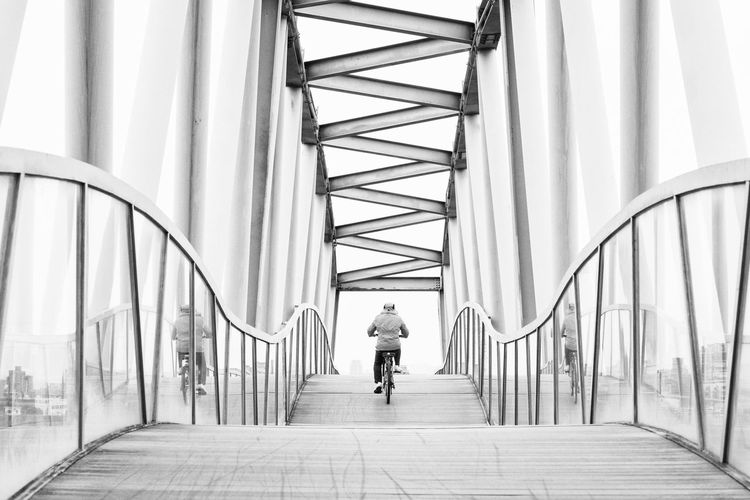 Rear view of person cycling on bridge