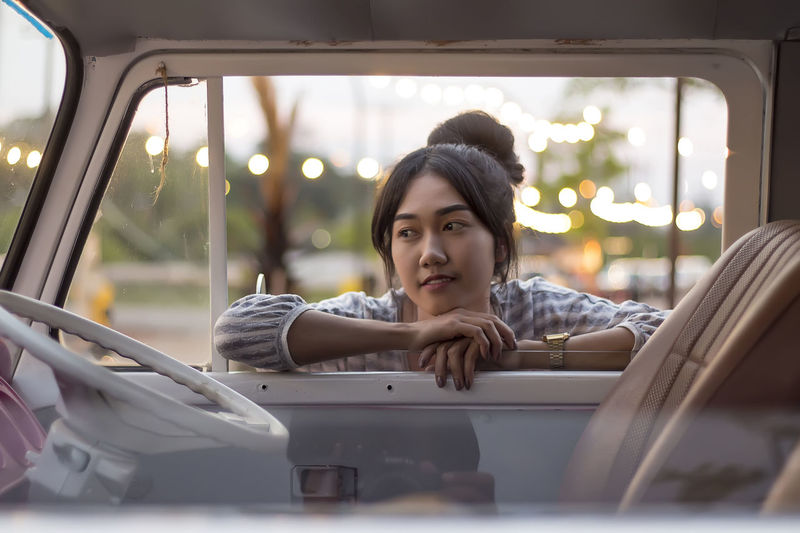 Thoughtful young woman leaning on car window at dusk