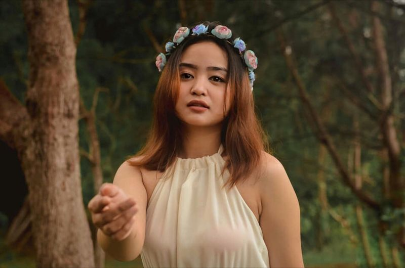 Portrait of beautiful young woman gesturing against trees in forest