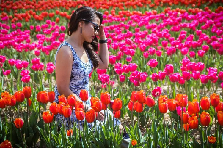 Woman Kneeling Amidst Tulips On Field
