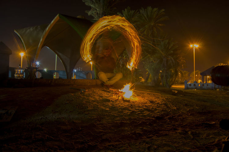 Man sitting at campfire with light painting during night