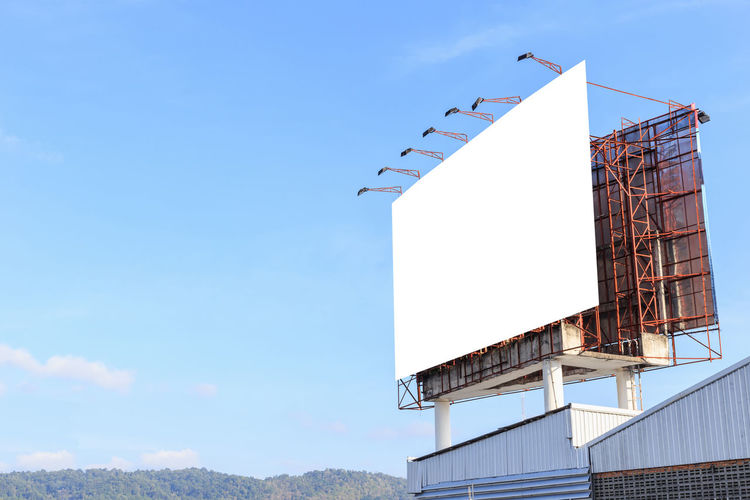 Low angle view of blank billboard against sky
