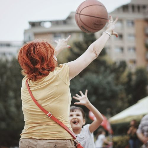 Rear View Of Woman Playing Basketball In City